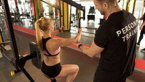 Personal trainer giving advice to trainee how to work out on fly chest machine royalty free stock photography