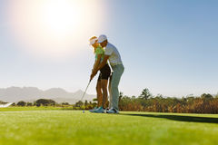 Personal trainer giving lesson on golf course Stock Photos