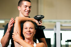 Personal Trainer in gym. Woman with her personal fitness trainer in the gym exercising with dumbbells Royalty Free Stock Photography