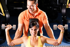 Personal Trainer in gym. Woman with her personal fitness trainer in the gym exercising with dumbbells Stock Images