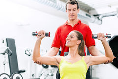 Personal trainer in gym Stock Image