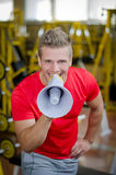 Personal trainer in gym yelling with megaphone towards camera. Young, male personal trainer in gym yelling with megaphone towards camera, smiling Stock Images