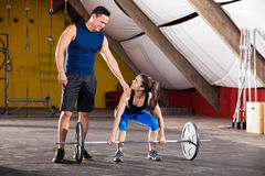 Personal trainer in a gym. Young Hispanic men giving some advice on her workout to a cute girl in a cross-training gym Stock Photo