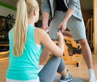Personal trainer handing dumbbells to young woman during workout session Stock Photography