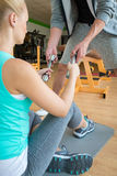Personal trainer handing dumbbells to young woman during workout session Stock Image
