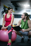 Personal trainer having a training consultation with a client. T. Personal trainer having a training consultation with a client Stock Image