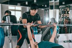 Personal trainer help a woman lift a barbell royalty free stock photo