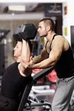 Personal trainer helping athletic man Royalty Free Stock Image