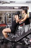Personal trainer helping athletic man Stock Images