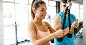 Personal trainer helping. Beautiful women in gym Stock Image