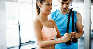 Personal trainer helping. Beautiful women in gym Stock Images