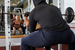Personal trainer helping blonde woman in squats Stock Image