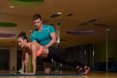 Personal Trainer Helping Client In Gym With Push-ups. Personal Trainer Showing Young Woman How To Train Push-ups In The Gym Royalty Free Stock Photo