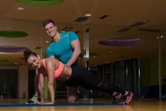 Personal Trainer Helping Client In Gym With Push-ups. Personal Trainer Showing Young Woman How To Train Push-ups In The Gym Stock Image
