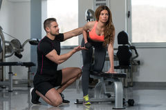 Personal Trainer Helping Client In Gym. Personal Trainer Showing Young Woman How To Train Back Exercise With Dumbbell In A Gym Stock Images