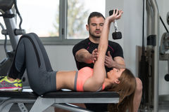 Personal Trainer Helping Client In Gym. Personal Trainer Showing Young Woman How To Train Chest Exercise With Dumbbell In A Gym Stock Photography