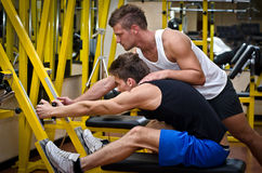 Personal trainer helping client in gym Royalty Free Stock Image
