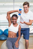 Personal trainer helping client lift dumbbell on exercise ball. At the gym Stock Photos