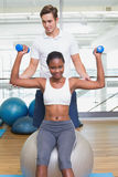 Personal trainer helping client lift dumbbell on exercise ball. At the gym Royalty Free Stock Photography
