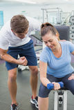 Personal trainer helping client lift dumbbell. At the gym Stock Photography