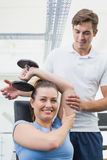 Personal trainer helping client lift dumbbell. At the gym Stock Images