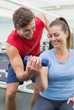 Personal trainer helping client lift dumbbell. At the gym Royalty Free Stock Images