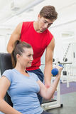 Personal trainer helping client lift dumbbell. At the gym Stock Image