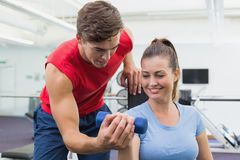 Personal trainer helping client lift dumbbell. At the gym Royalty Free Stock Photo