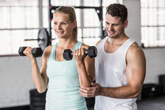 Personal trainer helping client lift dumbbells. In crossfit gym Stock Image