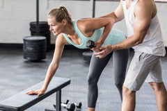Personal trainer helping client lift dumbbells. In crossfit gym Royalty Free Stock Photos