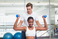 Personal trainer helping client lift dumbbells on exercise ball. At the gym Stock Photos