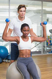 Personal trainer helping client lift dumbbells on exercise ball. At the gym Stock Image