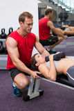 Personal trainer helping client lift dumbbells. At the gym Stock Images