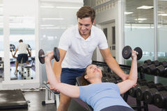 Personal trainer helping client lift dumbbells. At the gym Stock Photo