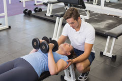 Personal trainer helping client lift dumbbells. At the gym Stock Photos