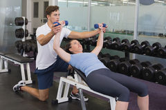 Personal trainer helping client lift dumbbells. At the gym Royalty Free Stock Image