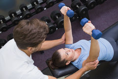 Personal trainer helping client lift dumbbells. At the gym Stock Photography