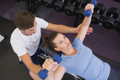 Personal trainer helping client lift dumbbells. At the gym Royalty Free Stock Photography