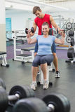 Personal trainer helping client lift dumbbells. At the gym Stock Image