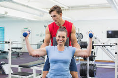 Personal trainer helping client lift dumbbells. At the gym Royalty Free Stock Photo