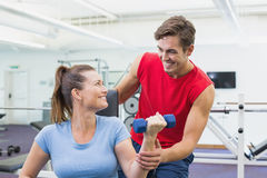 Personal trainer helping client lift dumbbells. At the gym Royalty Free Stock Photos