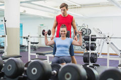 Personal trainer helping client lift dumbbells. At the gym Royalty Free Stock Images