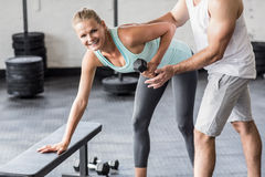 Personal trainer helping client lift dumbbells Royalty Free Stock Image
