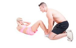 Personal trainer helping fitness woman to make crunches Royalty Free Stock Photos