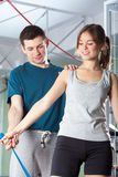 Personal trainer helping girl during exercises Royalty Free Stock Photos