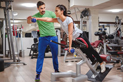 Personal trainer helping girl to train shoulders Royalty Free Stock Images