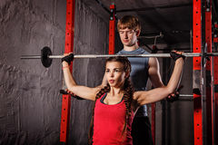 Personal trainer helping girl. Personal trainer helping girl work the pole. Sport Club. Fitness club. Healthy lifestyle concept Stock Image