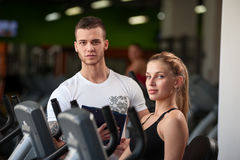 Personal trainer helping his female client in gym. Personal trainer helping his female client on machine. Attractive blonde women working out in gym with the Stock Photo