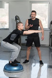 Personal Trainer Helping Man On Bosu Balance Ball. Personal Trainer Showing Young Man How To Train On Bosu Balance Ball In A Gym Royalty Free Stock Photo