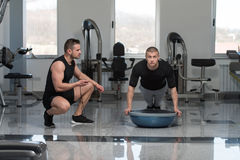 Personal Trainer Helping Man On Bosu Push Ups. Personal Trainer Showing Young Man How To Train On Bosu Push Ups In A Health And Fitness Concept Stock Image